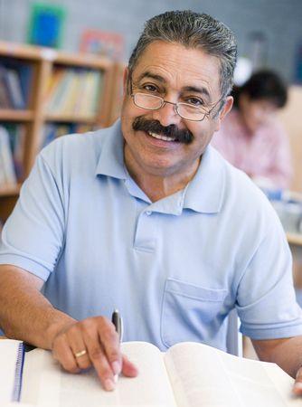 educating: Hombre sentado en la biblioteca con un libro y cuaderno (atenci�n selectiva) Foto de archivo