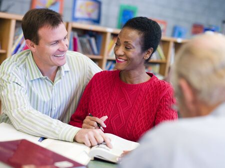 Man and woman sitting in library near another man with a book and notepad (selective focus) Stock Photo - 3194542