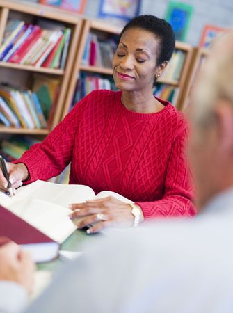 Woman sitting near a man in library with a book and notepad (selective focus) photo