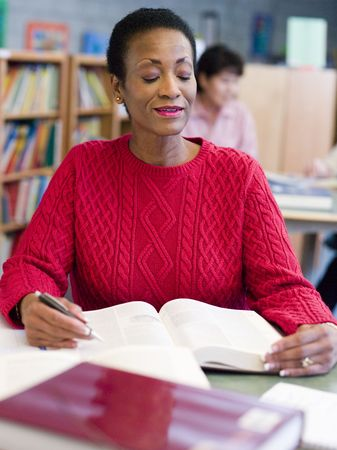 Woman sitting in library with a book (selective focus) photo