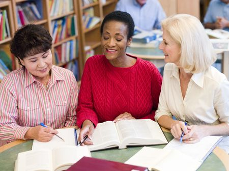 Three women sitting in library with books and notepads (selective focus) photo