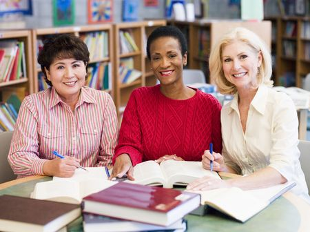 group study: Three women sitting in library with books and notepads (selective focus) Stock Photo