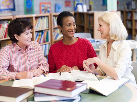 female senior adults: Three women sitting in library with books and notepads (selective focus) Stock Photo