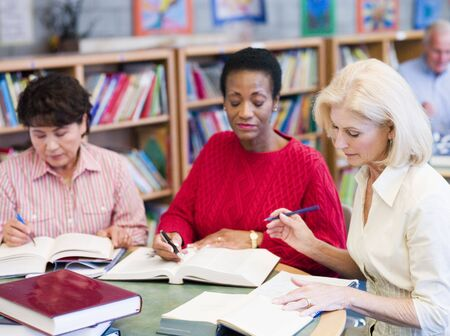 Three women sitting in library with books and notepads (selective focus) Stock Photo