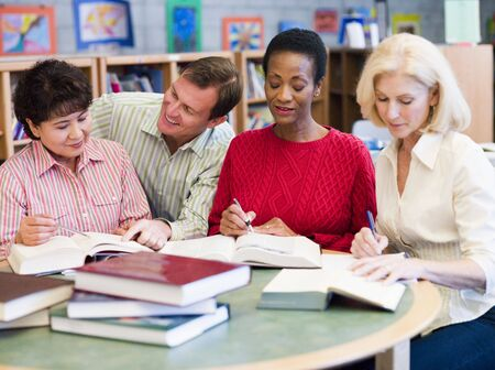 Three women sitting in library with books and notepads while a man leans over them (selective focus) photo