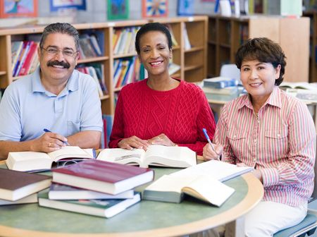 eye pad: Three people sitting in library with books and notepads (selective focus) Stock Photo