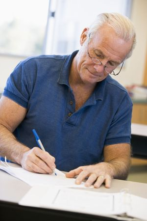 offset up: Adult student in class taking notes Stock Photo