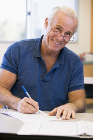 40s: Adult student in class taking notes Stock Photo