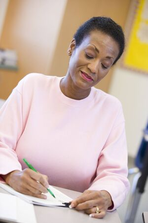 writing black: Adult student in class taking notes Stock Photo