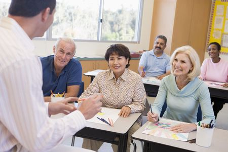 male senior adult: Adult students in class drawing pictures with teacher in foreground (selective focus) Stock Photo