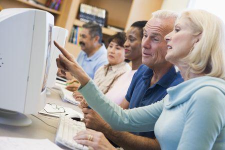 tercera edad: Cinco personas a terminales de computadora en la biblioteca (profundidad de campo) Foto de archivo