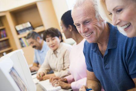 mature people: Cinque persone a terminali di computer in biblioteca (profondit� di campo)