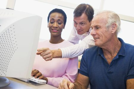 Three people at a computer terminal (depth of field/high key) Stock Photo - 3194602