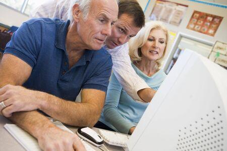 uses computer: Three people at computer terminal