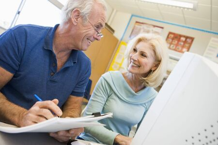 frontal views: Two people at computer terminal with notepad Stock Photo