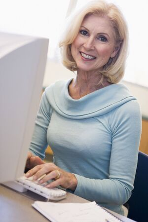 Woman sitting at computer typing (high key) Stock Photo - 3194584