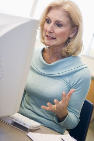 uses a computer: Woman sitting at computer frustrated (high key)