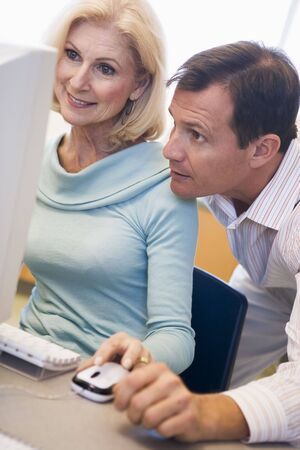 Dos personas frente a la computadora buscando en monitor (clave de alta)  Foto de archivo - 3194634