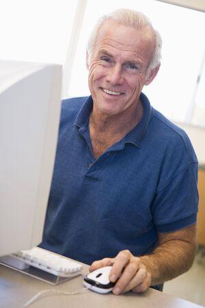 frontal views: Man at computer smiling (high key)