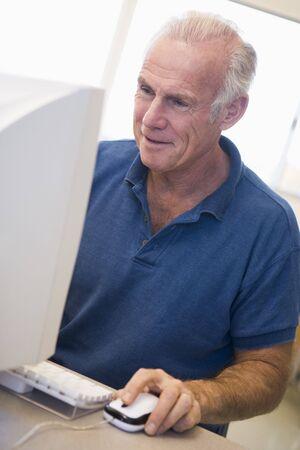 offset angle: Man at computer smiling and looking at monitor (high key)