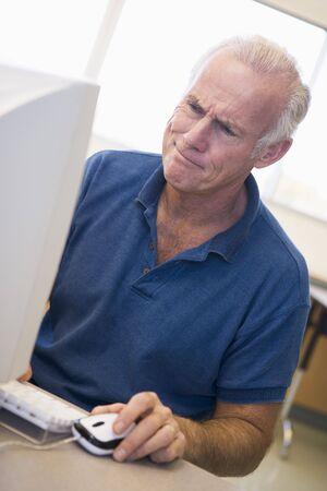 uses computer: Man at computer looking at monitor confused (high key)