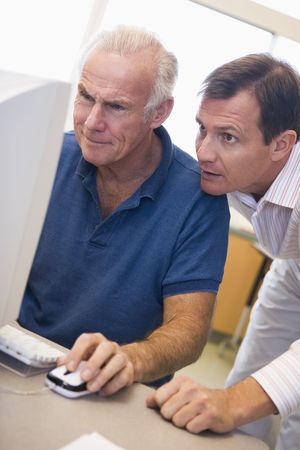 adult only: Two men at computer looking at monitor (high key) Stock Photo