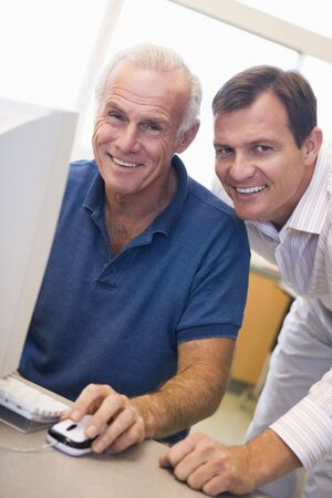 mentors: Two men at computer smiling (high key)