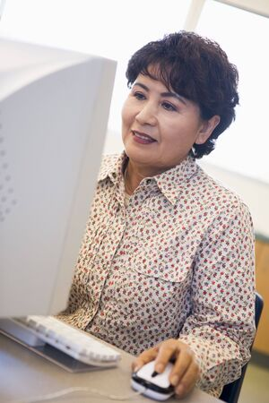 uses a computer: Woman at computer smiling and looking at monitor (high key)