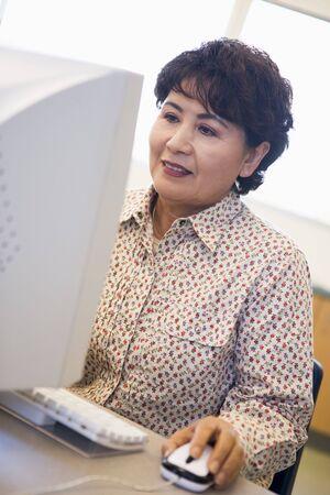 uses computer: Woman at computer smiling and looking at monitor (high key)