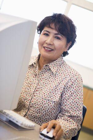 one senior adult woman: Mujer a equipo sonriendo y mirando a monitor (clave de alta)