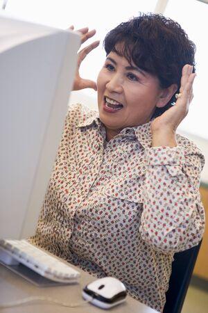 uses computer: Woman at computer looking at monitor surprised (high key) Stock Photo