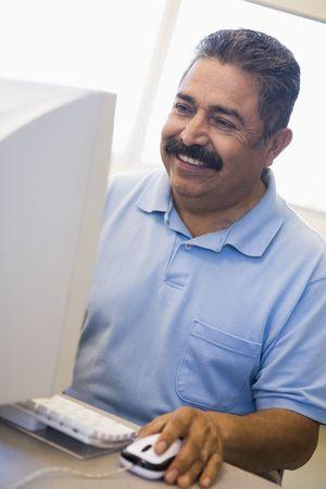 Man at computer smiling and looking at monitor (high key) photo