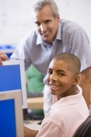 early teens: Teacher with male student in computer class Stock Photo