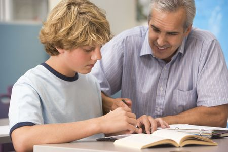 early teens: Teacher giving personal instruction to male student