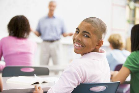 estudiante de secundaria: Hombre de estudiantes con otros estudiantes en el aula  Foto de archivo