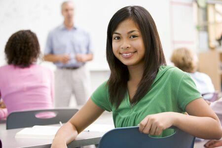 estudiante de secundaria: Femenino de los estudios con otros estudiantes en el aula  Foto de archivo