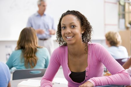 faculty: Female student with other students in classroom Stock Photo