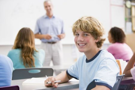 Male student with other students in classroom photo
