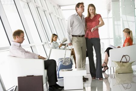 luggage airport: Couple waiting with other airline passengers in departure gate Stock Photo