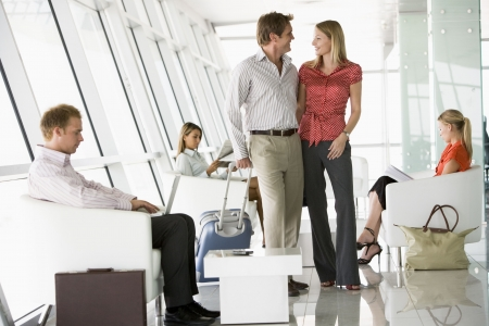 business traveler: Couple waiting with other airline passengers in departure gate Stock Photo