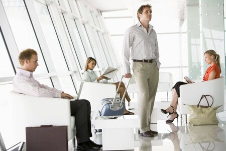 Male airline passenger waiting with other passengers in departure gate photo