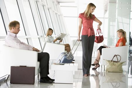 Female airline passenger waiting with other passengers in departure gate photo