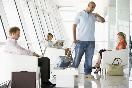 luggage airport: Male airline passenger waiting with other passengers in departure gate