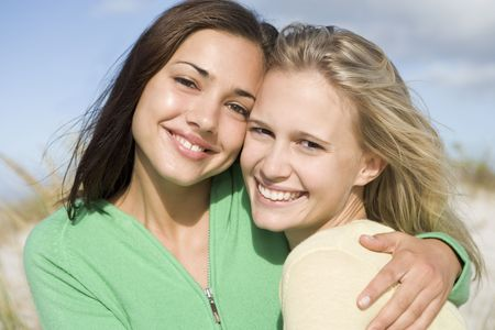 friend hug: Two young women posing outdoors