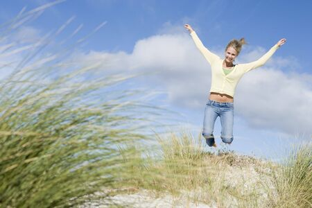 blond streaks: Young woman jumping on a sand hill