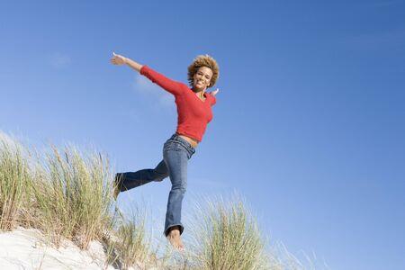 low angle views: Joven mujer saltando sobre una colina de arena