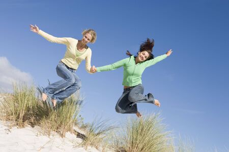 only teenage girls: Young woman jumping on a sand hill