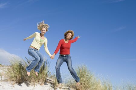 girls at the beach series: Young woman jumping on a sand hill