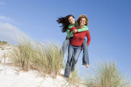 girls at the beach series: Young woman giving piggyback ride to her friend on a sand hill Stock Photo