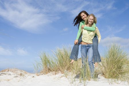 carrying girlfriend: Young woman giving piggyback ride to her friend on a sand hill Stock Photo